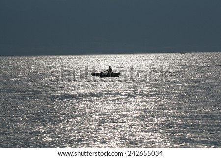 Silhouette of a fishing boat at sunrise out of the coast. Fisherman on the sea in the beautiful morning.