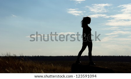 Silhouette of a fit healthy sexy woman standing on the horizon against a late afternoon sky with plenty of copyspace - stock photo