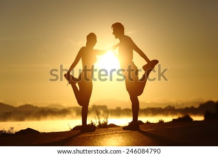 Silhouette of a fitness couple profile stretching at sunset with the sun in the background - stock photo