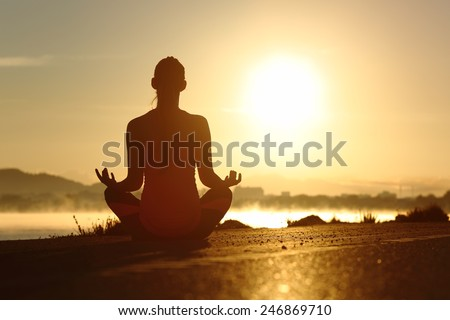 Silhouette of a fitness woman exercising yoga meditation exercises with the sun in the background - stock photo