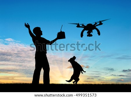 Silhouette of a flying drone, and a man with a remote control and dog at sunset. Concept quadrocopters