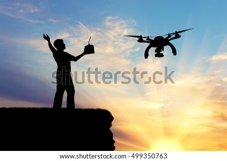 Silhouette of a flying drone, and a man with a remote control on the mountain. Concept quadrocopters