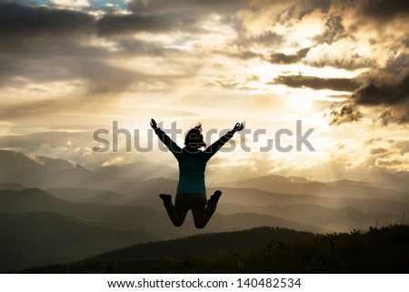 Silhouette of a freedom young jumping woman on the mountain Carpathians