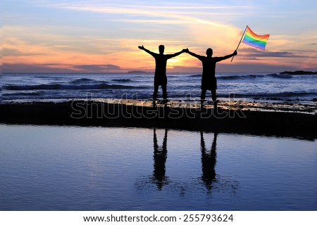Silhouette of a gay couple holding a rainbow pride flag at sunset.  - stock photo