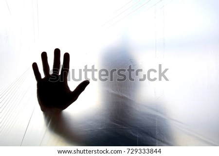 Silhouette of a ghost hand behind transparent plastic