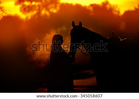 Silhouette of a girl and a horse on a background of dawn. A man standing near a horse that breathes steam.