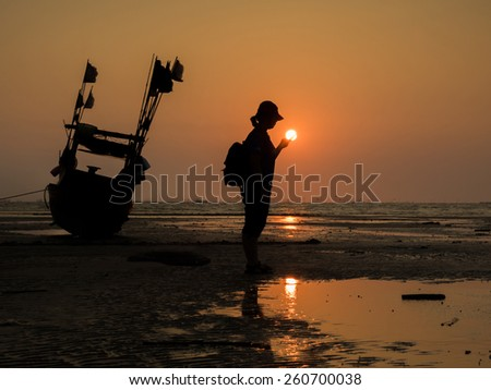 Silhouette of a girl and fishing boat  in sunset on the beach