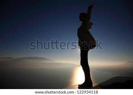 silhouette of a girl enjoying the view from a very high spot - stock photo