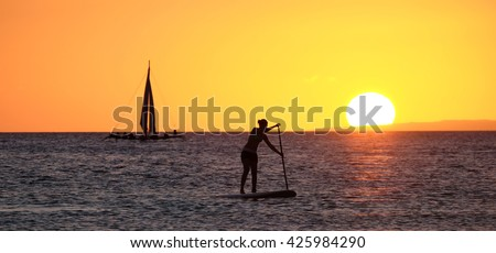 Silhouette of a girl floating on on the sup surfboard at amazing orange sunset over the sea  at Boracay island Philippines