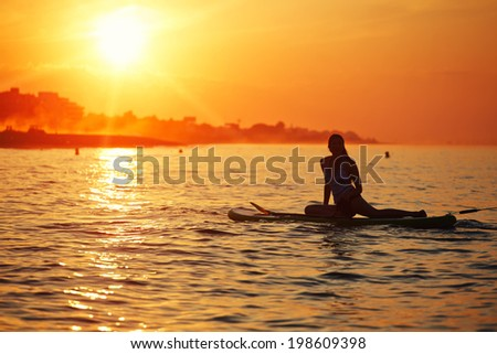 Silhouette of a girl floating on the sea with surf board on the excellent background of orange sunset