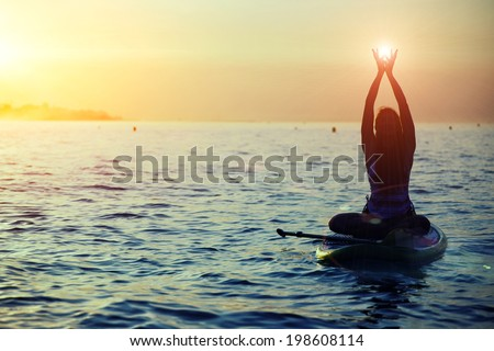 Silhouette of a girl holding sun in the hands on sup yoga meditation, harmony with the nature in yoga meditation during beautiful dawn - stock photo