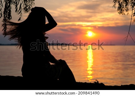 silhouette of a girl in a dress on the beach at sunset