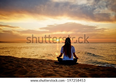 Silhouette of a girl in a sitting yoga pose in the evening sunset
