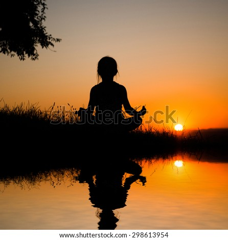 silhouette of a girl in lotus pose on the background of beautiful sunset sky