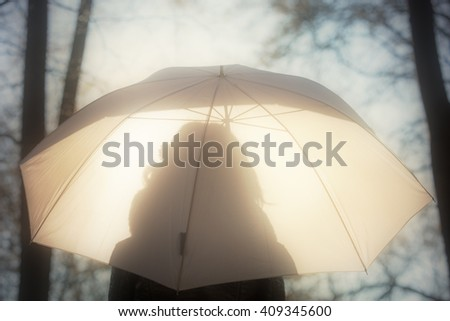 Silhouette of a girl in nature with a white and transparent umbrella. - stock photo