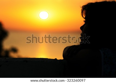 silhouette of a girl looking at the sunset at sea