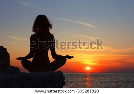 silhouette of a girl meditating at sunset.