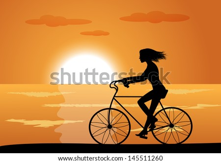 silhouette of a girl on a bike ride on the background of the sea and the sunset - stock photo