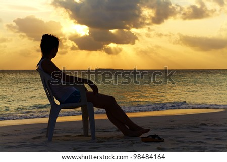 Silhouette of a girl on a chair against a beautiful sunset in the ocean, Maldives