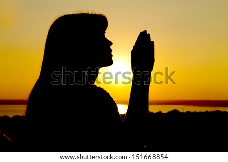 silhouette of a girl raises her hands to God - stock photo