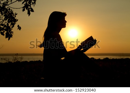 silhouette of a girl reading at sunset - stock photo
