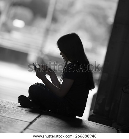 Silhouette of a girl using her tablet computer.  There may  be a predator trying to get to her. - stock photo