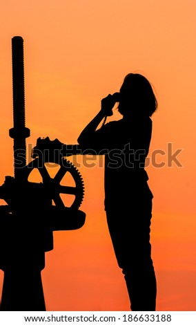 Silhouette of a girl using telephone