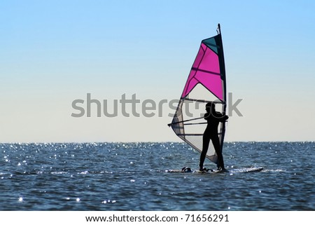 Silhouette of a girl windsurfer on the sea