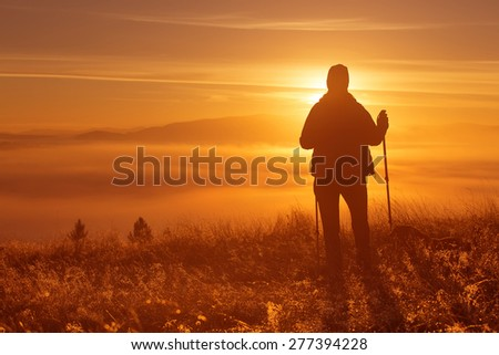 Silhouette of a girl with a lonely sport Trekking pole in the morning fog. Landscape composition, background mountains and sunrise. - stock photo