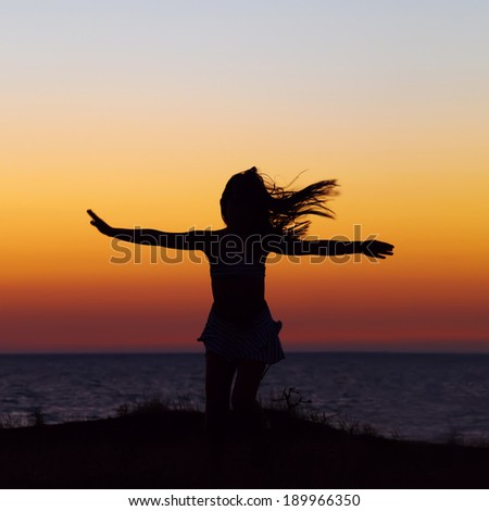 silhouette of a girl with flying hair and arms outstretched on the sea background. sunset outdoors. summer child - stock photo