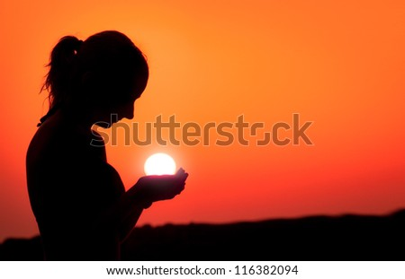 Silhouette of a girl with the sun in her hands, - stock photo