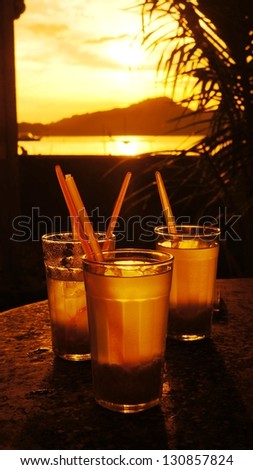 Silhouette of a Glass of drink on the see shore in a lovely evening sunset. - stock photo