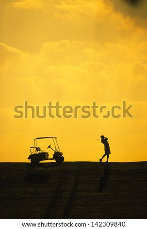 Silhouette of a golf cart and a golfer swinging a club. - stock photo