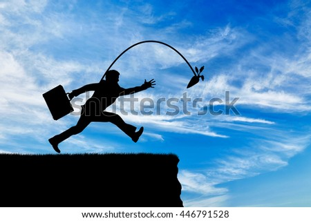 Silhouette of a greedy man running after a carrot without noticing the abyss. Concept of greed and money - stock photo