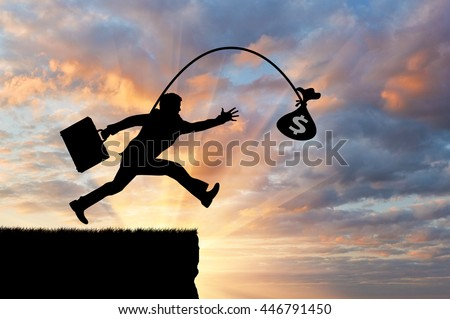 Silhouette of a greedy man running by looking at money, not noticing the abyss. Concept of greed and money - stock photo