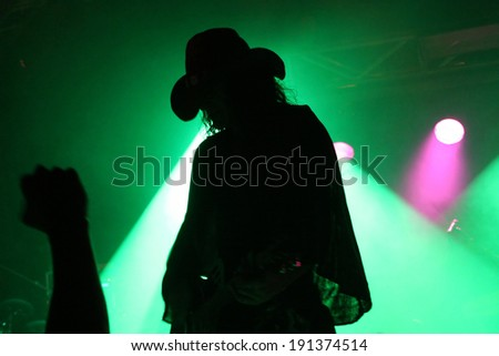 Silhouette of a guitarist on stage with a cowboy hat with fan's fist in front of green reflector - stock photo