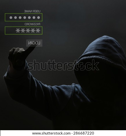 Silhouette of a hacker, Male thief typing password on virtual screen - computer hacker - stock photo