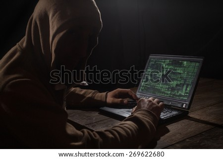 Silhouette of a hacker with laptop - stock photo
