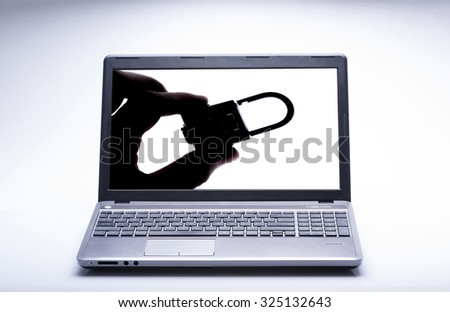 Silhouette of a hand holding a padlock on a laptop computer for security concept