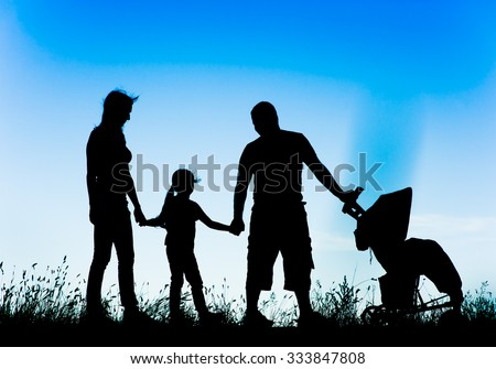 silhouette of a happy family walking with stroller - stock photo