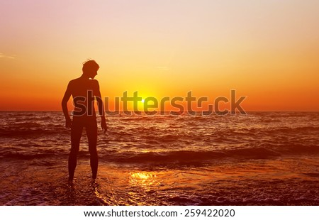 silhouette of a happy man admires the sunset on the sea. healthy lifestyle. freedom and inspiration