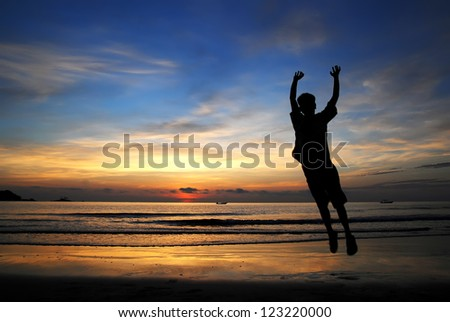 Silhouette of a happy man jumping by the beach in the morning - stock photo