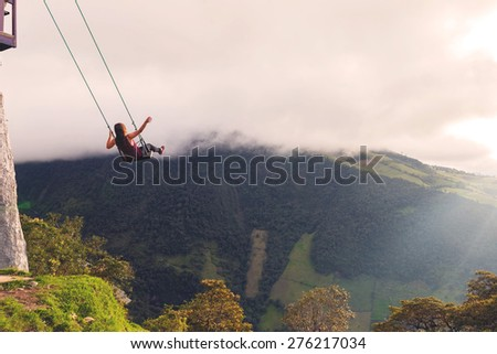Silhouette Of A Happy Young Blonde Woman Swinging On A Swing Above The Andes Mountains, Casa Del Arbol, Tree House,  Ecuador, South America  - stock photo