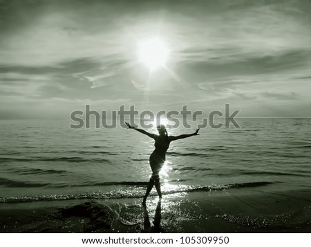 Silhouette of a happy young girl / woman in the water at sunset - stock photo