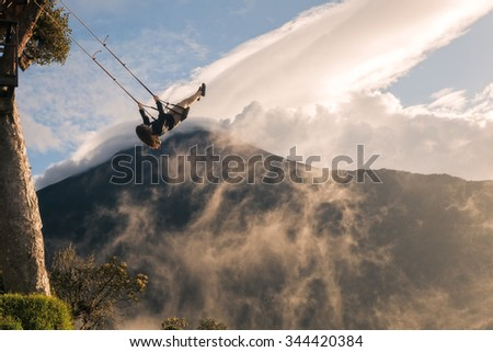 Silhouette Of A Happy Young Teenager Girl Swinging On A Swing Above The Andes Mountains, Tungurahua Volcano In The Background - stock photo