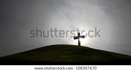 Silhouette of a holy christian crucifix illuminated by sunlight on top of a hill on a dramatic cloudy sky. - stock photo