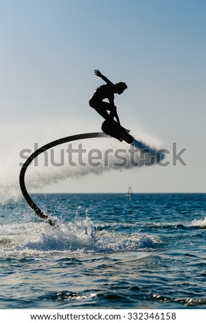 Silhouette of a hover board rider at sea - stock photo