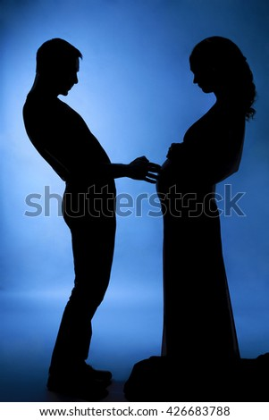 Silhouette of a husband and pregnant wife - stock photo
