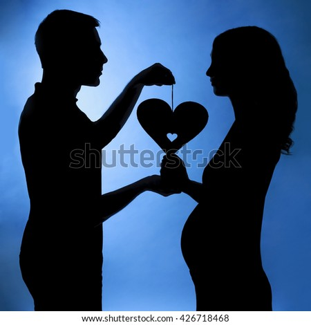 Silhouette of a husband and pregnant wife with a heart, love symbol - stock photo