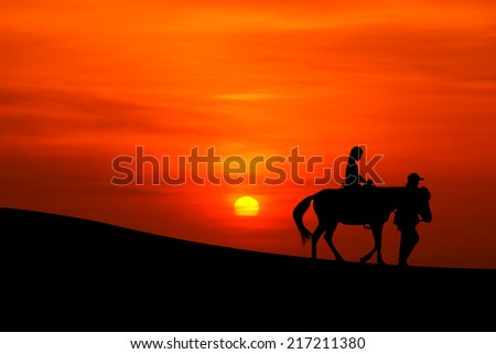 silhouette of a journey on horseback  with sunset - stock photo